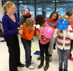Mentor helping several youth with balloons in a team building exercise