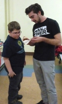 Mentor helping elementary boy with a project