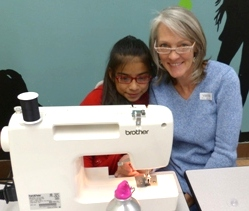 Mentor helping an elementary age girl with a sewing machine