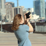 A teenage 4-H member shoots with her camera for photography project