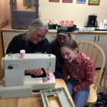 A leader shows 4-H members the sewing machine for their sewing projects